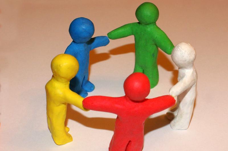 Fünf Knetmännchen in unterschiedlichen Farben stehen im Kreis und halten sich an den Händen