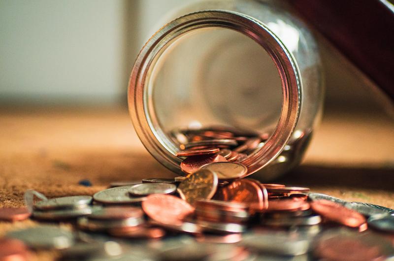 Münzen, die aus einem liegenden Glas fallen