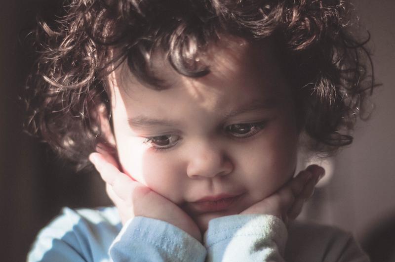 Nachdenkliches Kleinkind stützt den Kopf auf seine Hände