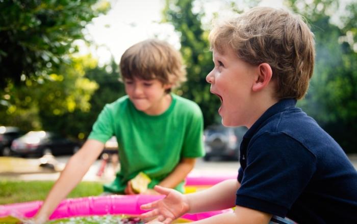 Zwei Jungen spielen am Planschbecken