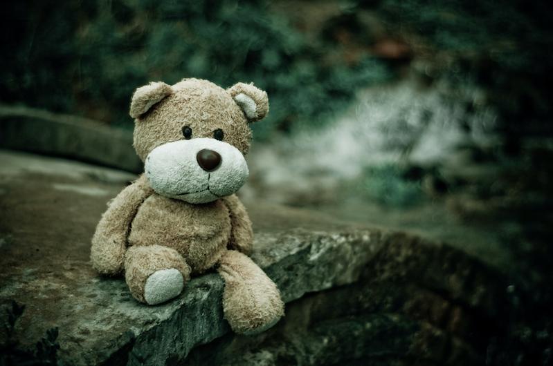 Ein Teddybär sitzt auf einem Stein