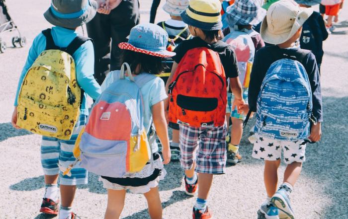 Kindergruppe von hinten, Kinder tragen Rücksäcke und Sonnenhüte