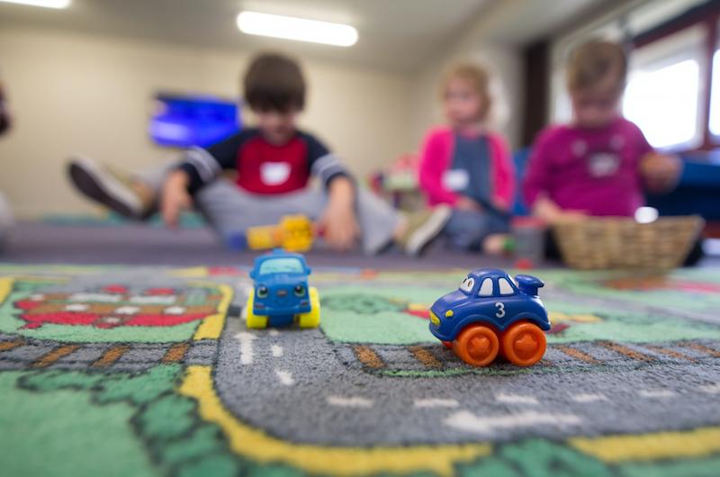 Spielteppich mit zwei Autos.Drei kleine Kinder unscharf im Hintergrund.