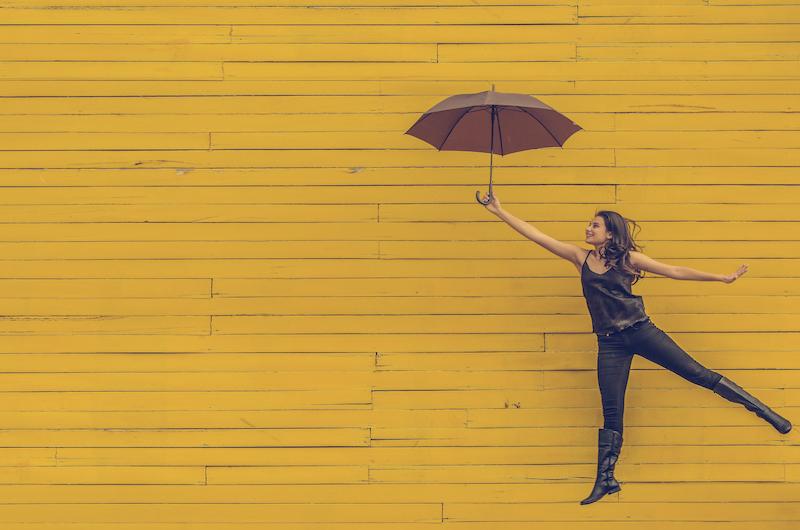 Springende junge Frau mit Schirm vor gelbem Hintergrund