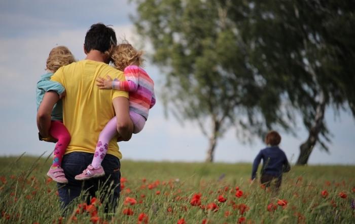 Mann von hinten mit zwei kleinen Kindern auf dem Arm, eines rennt vorweg