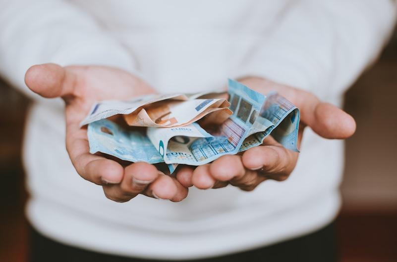 Geldscheine liegen auf ausgestreckten Händen
