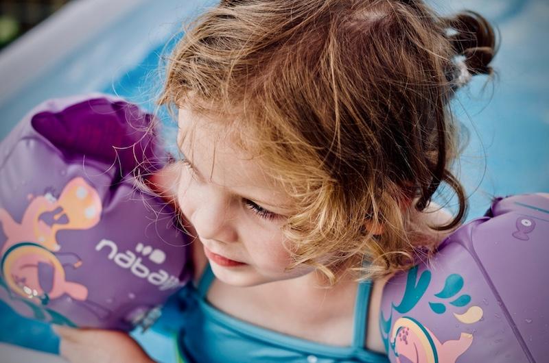 Kleines Mädchen mit Schwimmflügeln im Schwimmbad