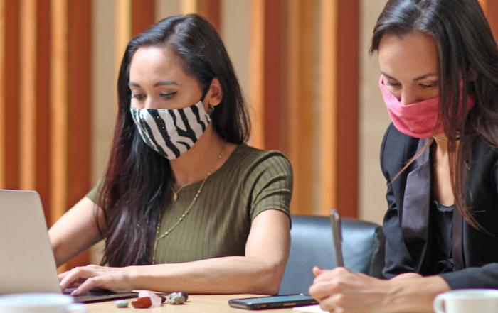Zwei jungen Frauen beim Ausfüllen von Befragungsbögen am Laptop sowie per Hand