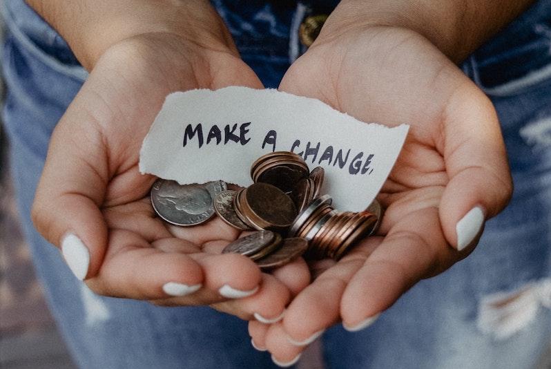 """Hände mit Kleingeld und Zettel """"make a change"""""""